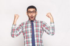 Happy winner handsome bearded businessman in checkered shirt, bl. Ue tie and black eyeglasses standing shouting and looking at camera with raised hands. indoor royalty free stock image
