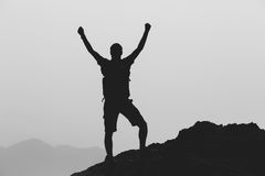 Happy winner reaching life goal success man. Success achievement climbing or hiking accomplishment business concept with man celebrating with arms up, raised Royalty Free Stock Photo