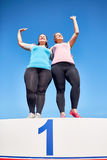 Happy winners. Two plus-size women standing on podium with number one and greeting fans Royalty Free Stock Photos