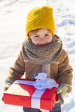 Happy winter child hold gift bow snow background. Cute boy in winter clothes hat and scarf close up. Winter holidays. Concept. May you have wonderful holiday royalty free stock photo