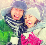 Happy winter couple with hot drinks outdoors. Happy winter couple having fun outdoors. Hot drinks Royalty Free Stock Images