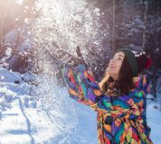 Happy winter fun woman throwing snow banner. Panorama crop of outdoor lifestyle girl playing in snow outside laughing in. Yellow coat, hat, gloves and scarf royalty free stock images