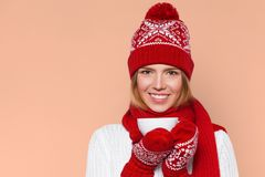 Happy winter girl in knitted warm hat and mittens holding a cup in hands. Smilling Christmas woman, isolated Royalty Free Stock Photos