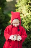 Happy winter girl in red coat sitting beside Christmas tree and holding Present box. royalty free stock images