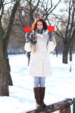 Happy winter girl with two red hearts standing on bench Royalty Free Stock Image