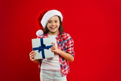 Happy winter holidays. Small girl. Present for Xmas. Childhood. Christmas shopping. Little girl child in santa red hat. New year party. Santa claus kid stock image