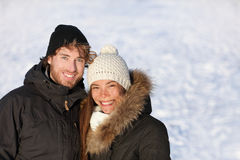 Happy winter interracial couple outdoors portrait. Cute young adults smiling in warm outerwear knit hat and down coats outside. Asian chinese woman, Caucasian stock photography