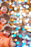 Happy winter kids against colorful lights royalty free stock photography