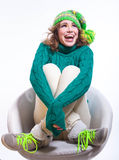 Happy winter mood. Happy female model wearing jeans, warm knitted sweater with beautiful pattern, shoes with green laces and bright colorful green yellow knitted Stock Photography