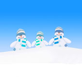 Happy winter  snowmen family against blue sky Stock Photography