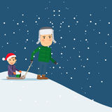 Happy winter time. Dad and son sledding Royalty Free Stock Photo