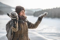 Happy hipster girl in snow. Happy winter time in the mountains with girl walking with backpack. Enjoying snowfall, expressing positivity, smiling to camera stock photos