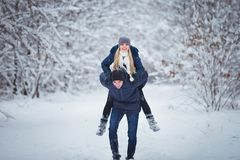 Happy winter travel couple. Man giving woman piggyback ride on winter vacation in snowy forest. Happy winter travel couple. Man giving women piggyback ride on Stock Images