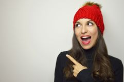 Happy winter woman with red hat looking to the side and pointing with her finger your product on gray background. Copy space. stock image
