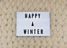HAPPY WINTER word on lightbox on knit background. Cozy compozition. Knit background. HAPPY WINTER word on lightbox on knit background. Cozy compozition. Knit royalty free stock image