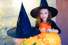 Happy witch children during Halloween party. Playing around the table with pumpkins Royalty Free Stock Photos