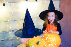 Happy witch children during Halloween party. Playing around the table with pumpkins Royalty Free Stock Photo