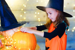 Happy witch children during Halloween party. Playing around the table with pumpkins Stock Photography