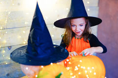 Happy witch children during Halloween party. Playing around the table with pumpkins Stock Photos