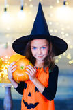 Happy witch children during Halloween party. Playing around the table with pumpkins Royalty Free Stock Photography