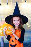 Happy witch children during Halloween party. Playing around the table with pumpkins Royalty Free Stock Images