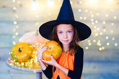 Happy witch children during Halloween party. Playing around the table with pumpkins Stock Images