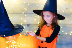 Happy witch children during Halloween party. Playing around the table with pumpkins Royalty Free Stock Image
