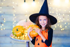 Happy witch children during Halloween party. Playing around the table with pumpkins Stock Image