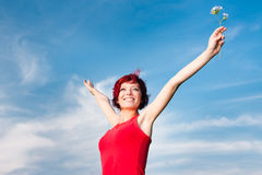 Happy Woman. A happy woman in red holding a flower, on the backdrop of blue sky Stock Image