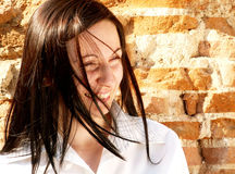 Happy woman. Happy business woman with hair blowing in the wind on a brickwall royalty free stock photo