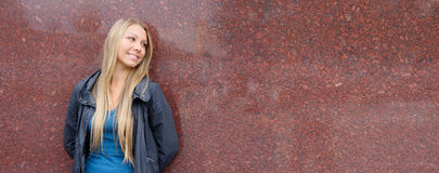 Happy woman. Happy young woman on a background of a wall. panoramic view Stock Images