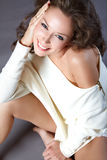 Happy woman. Portrait of the happy young woman in a white sweater. She smiles. She has beautiful white teeth Royalty Free Stock Photo