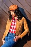 Happy woman. Standing next to a brown door Stock Photo