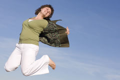 Happy woman. Voluptuous woman jumping in the sky, happy because spring is coming Stock Image