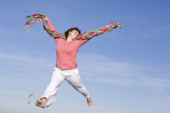 Happy woman. Voluptuous woman jumping in the sky, happy because spring is coming Royalty Free Stock Photos