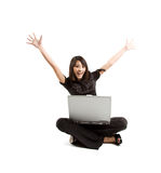 Happy woman. A happy woman raising her arms while working on her laptop Stock Image