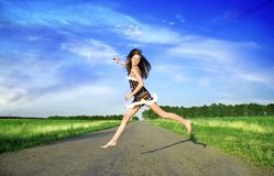 Happy woman. Jumping over the road under blue sky Royalty Free Stock Image