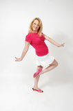 Happy woman. Woman sticks arms to the side and lifts her foot for a cute pose. Full body on white background. Happy woman Stock Photo
