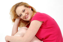 Happy woman. Blond happy woman smiling while she sits on the floor and bends over her knees Royalty Free Stock Photography
