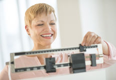 Happy Woman Adjusting Balance Weight Scale. Happy mature woman adjusting balance weight scale at health club royalty free stock image