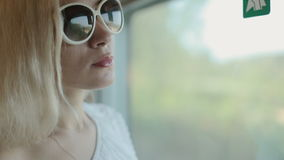 Happy woman admire the view from the window of a moving train. Happy woman in sunglasses admire the view from the window of a moving train stock footage