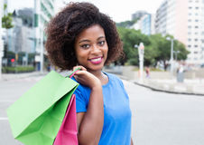 Happy woman from Africa with shopping bags. In city in the summer royalty free stock images