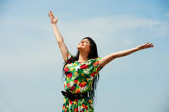 Happy woman against blue sky Stock Photo