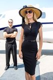 Happy Woman Against Bodyguard And Private Jet. Happy women in elegant dress with bodyguard and private jet in background royalty free stock photography
