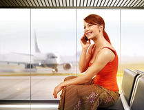 Happy woman in airport. Beautiful traveler with mobile phone in airport Stock Images