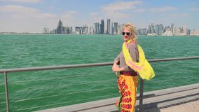 Woman by seascape of Doha. Happy woman along the Doha Bay looking cityscape on background. Lifestyle caucasian tourist enjoys skyscrapers of Doha Downtown stock footage