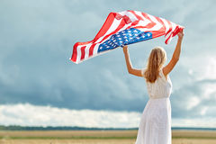 Happy woman with american flag on cereal field Royalty Free Stock Images