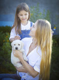 Happy Woman And Her Daughter With Puppy Of Labrador Stock Photography