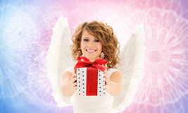 Happy woman with angel wings and birthday gift. People, holidays and birthday concept - happy young woman with angel wings holding gift box over rose quartz and Stock Images