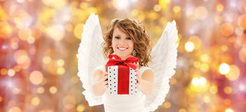Happy woman with angel wings and christmas gift. People, holidays, christmas and birthday concept - happy young woman with angel wings holding gift box over royalty free stock photo
